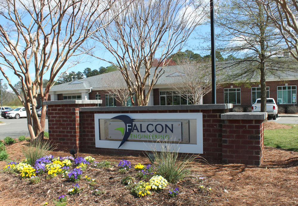 Sign surrounded by flowers at exterior of Falcon headquarters